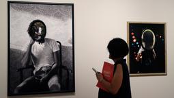 Seorang wanita mengamati karya seni Todd Gray pada pameran 'Michael Jackson: On The Wall' di National Potrait Gallery, London, Rabu (27/6). Dalam pameran ini, karya-karya yang dihasilkan lebih dari 40 seniman dipamerkan. (AP/Kirsty Wigglesworth)