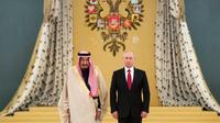 Presiden Rusia, Vladimir Putin dan Raja Arab Saudi Salman bin Abdulaziz Al Saud mendengarkan lagu kebangsaan di Kremlin, Moskow, Rusia (5/10). Raja Salman tercatat sebagai raja Saudi pertama yang menjejakkan kaki ke Rusia. (AP Photo/Pavel Golovkin)