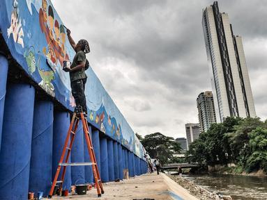 """Seniman saat menyelesaikan pembuatan mural di turap Kanal Banjir Barat, Jakarta, Rabu (13/1/2021). Pembuatan mural bertemakan """"Kehidupan Sungai"""" yang dikerjakan oleh seniman dari Komunitas Mural Depok tersebut bertujuan mempercantik lingkungan di sekitar Kali Ciliwung. (merdeka.com/Iqbal S. Nugroho)"""