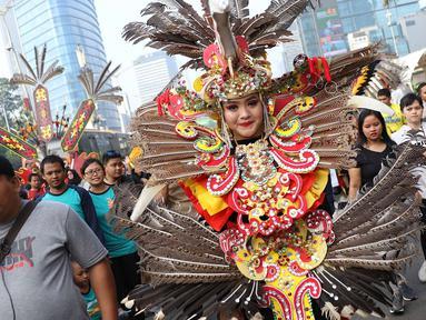 Seorang wanita dari kelompok seni budaya Kalimantan Selatan mengenakan pakaian adat berpawai saat pelaksanaan car free day, Jakarta, Minggu (1/7). Pawai tersebut diadakan untuk mengenalkan budaya Kalsel kepada masyarakat. (Liputan6.com/Immanuel Antonius)