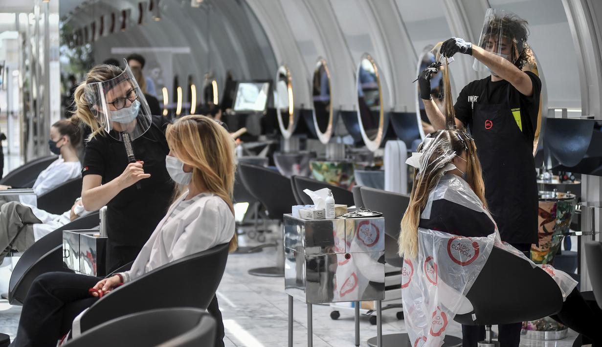 Pengunjung mendapat perawatan rambut di sebuah salon di Milan, Italia, Senin (18/5/2020). Italia secara perlahan melonggarkan kebijakan lockdown akibat pandemi virus corona COVID-19. (Claudio Furlan/LaPresse via AP)