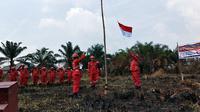 Personel Manggala Agni mengibarkan bendera dalam upacara kemerdekaan di lokasi kebakaran lahan. (Liputan6.com/M Syukur)