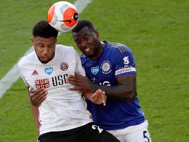 Penyerang Sheffield United, Lys Mousset melompat saat berebut bola dengan bek Leicester City, Wes Morgan dalam lanjutan Liga Inggris pekan ke-36 di Stadion King Power, Kamis (16/7/2020). Leicester City sukses menggulung tamunya, Sheffield United dengan skor 2-0. (David Davies/Pool via AP)