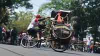 Salah seorang peserta lomba balap becak melakukan atraksi mengangkat roda. (Liputan6.com/Huyogo Simbolon)