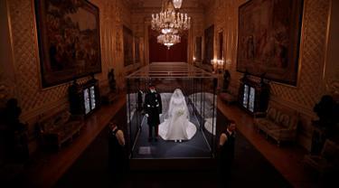 "Petugas berjaga dekat gaun pernikahan Meghan Markle dan Pangeran Harry yang ditampilkan pada pameran ""A Royal Wedding: The Duke and Duchess of Sussex"" di Kastil Windsor, London, 25 Oktober 2018. Pameran ini dibuka hingga Januari 2019. (AP/Matt Dunham)"
