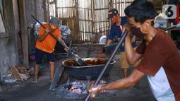 Pekerja mengaduk adonan dodol di pabrik dodol Betawi Mugi Jaya, Cilenggang, Tangerang Selatan, Rabu (13/5/2020). Produksi dodol selama pandemi Covid-19 menggunakan dua tungku. (Liputan6.com/Fery Pradolo)