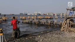 Pekerja menyelesaikan pondasi dermaga di Muara Angke, Jakarta Utara, Rabu (3/7/2019). Pembangunan dermaga tersebut untuk melindungi kapal-kapal yang bersandar di dermaga dari hantaman ombak besar. (Liputan6.com/Faizal Fanani)