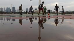 Sejumlah warga berebut bola saat olahraga sepak bola di Kawasan Monumen Nasional, Jakarta, Rabu (13/2). Monas merupakan salah satu lokasi yang kerap dijadikan ruang olahraga bagi warga ibukota. (Bola.com/M. Iqbal Ichsan)