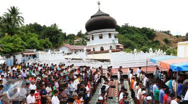 Sejumlah warga melaksanakan Salat Jumat di halaman Masjid Jami Quba, Pidie Jaya, Aceh, Jumat (9/12). Gempa berkekuatan 6,5 SR telah merobohkan ratusan bangunan termasuk Masjid Jami Quba. (Liputan6.com/Angga Yuniar)