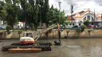 Pekerja menggunakan alat berat untuk mengeruk lumpur dan sampah yang mengendap di anak Sungai Ciliwung, Jakarta, Jumat (26/1). Pengerukan dilakukan untuk mencegah pendangkalan sungai. (Liputan6.com/Immanuel Antonius)