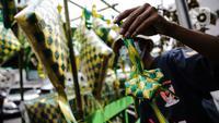 Pedagang memperlihatkan pernak-pernik ketupat hias dagangannya di Pasar Asemka, Jakarta, Selasa (4/5/2021). Pedagang mulai menjual pernak-pernik menjelang Lebaran seperti ketupat hias dengan harga mulai dari Rp15.000 hingga Rp60.000 tergantung ukuran. (Liputan6.com/Faizal Fanani)