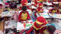 Nampak anak-anak dengan daya imajinasinya tengah mewarnai sketsa gambang burung Garuda di area PKEK Kamojang Garut, Jawa Barat (Liputan6.com/Jayadi Supriadin)