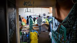 Seorang pria berjalan di gimnasium yang ditempati oleh para migran di lycee Jeanne-Bernard di Saint-Herblain, di luar Nantes, Prancis barat (28/3). Sekitar 250 imigran saat ini tinggal di tempat tersebut. (AFP Photo/Loic Venance)