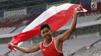 Atlet para-atletik Indonesia, Sapto Yogo Purnomo merayakan kemenangan lari nomor 100 meter T37 pria yang digelar di Stadion GBK, Jakarta, Selasa (9/10). Ini menjadi medali emas kedua Sapto di Asian Para Games 2018. (Liputan6.com/Helmi Fithriansyah)