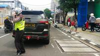Polantas memberhentikan mobil Toyota Fortuner hitam yang diduga menggunakan pelat nomor dinas Polri palsu di Jatinegara. (Istimewa)