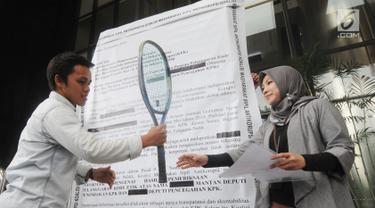 Aktivis ICW membawa replika surat raksasa dan raket diserahkan kepada KPK sebagai bentuk protes di Gedung KPK, Jakarta, Senin (26/8/2019). Mereka meminta KPK untuk memberikan laporan hasil dugaan pelanggaran etik mantan Deputi Penindakan KPK yang juga Capim KPK Firli Bahuri.(merdeka.com/Dwi Narwoko)