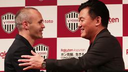 Mantan pemain Barcelona, Andres Iniesta (kiri) menyalami pemilik klub Vissel Kobe, Hiroshi Mikitani saat konferensi pers di Tokyo, Jepang, Kamis (24/5). Iniesta resmi bergabung dengan Vissel Kobe. (Behrouz MEHRI/AFP)