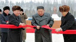 Pemimpin Korea Utara Kim Jong-un (kedua kanan) menggunting pita untuk menandai selesainya pembangunan Kota Samjiyon, Korea Utara, Senin (2/12/2019). Samjiyon merupakan sebuah kota baru yang dibangun di dekat Gunung Paektu. (STR/AFP/KCNA MELALUI KNS)