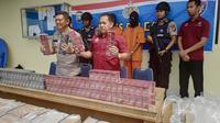 Direktur Polisi Air Polda Riau Komisaris Besar Badaruddin memperlihatkan tersangka dan barang bukti rokok tanpa cukai. (Liputan6.com/M Syukur)