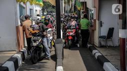 Pengunjung bersepeda motor antre untuk masuk ke Taman Mini Indonesia Indah (TMII), Jakarta, Sabtu (15/5/2021). Jumlah pengunjung dibatasi hanya 30 persen dari kapasitas normal dan hanya warga beridentitas DKI Jakarta yang boleh masuk. (Liputan6.com/Faizal Fanani)