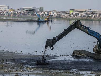 Alat berat mengeruk lumpur di Waduk Pluit, Jakarta, Rabu (30/10/2019). Waduk Pluit dikeruk untuk mengeluarkan lumpur yang mengendap pada bagian dasar. (Liputan6.com/ Faizal Fanani)