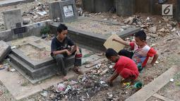 Anak-anak bermain layang-layang di TPU Menteng Pulo, Jakarta, Kamis (18/10). Padatnya pemukiman penduduk serta gedung bertingkat di kawasan tersebut menyebabkan anak-anak terpaksa bermain di tempat yang tidak semestinya. (Liputan6.com/Immanuel Antonius)
