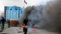 Demonstran Palestina membakar ban saat terjadi bentrokan menyusul demonstrasi di kota Ramallah Palestina (16/3). Mereka melakukan aksi menolak Yerusalem sebagai ibu kota Israel. (AFP Photo/Abbas Momani)