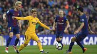 Striker Atletico Madrid, Antoine Griezmann, berusaha melewati kepungan pemain Barcelona pada laga La Liga Spanyol di Stadion Camp Nou, Barcelona, Minggu (4/3/2018). Barcelona menang 1-0 atas Atletico. (AFP/Lluis Gene)