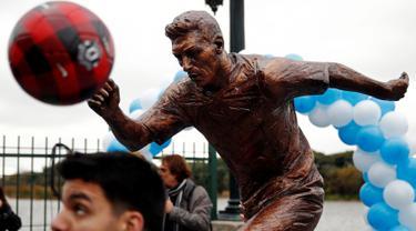 Seorang anak bermain bola di depan patung perunggu Lionel Messi yang baru diresmikan di pusat kota Buenos Aires, Argentina, Selasa (28/6). Patung tersebut guna membujuk Messi membatalkan keputusan pensiun yang sudah diambilnya. (REUTERS/Marcos Brindicci)