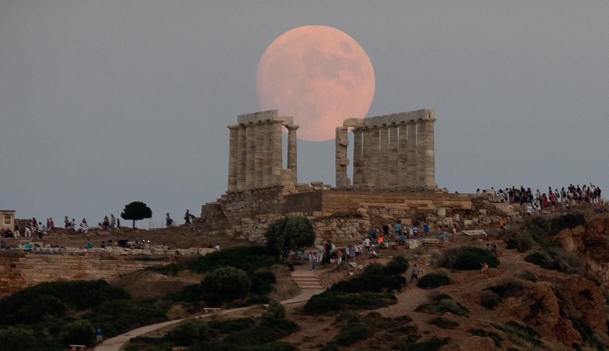 Bulan purnama hampir penuh yang menampakkan diri di langit Kuil Poseidon kuno di Cape Sounion, sekitar 70 kilometer sebelah tenggara Athena, Yunani (2/8/2020). (Xinhua/Marios Lolos)