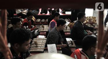 """Pengunjung berlatih menjadi Nayaga atau penabuh gamelan saat lokakarya """"Suara Dari Masa Lalu"""" di Museum Nasional, Jakarta, Minggu (22/12/2019). Lokakarya ini digelar dari 15 Desember 2019 hingga 5 Januari 2020. (merdeka.com/Iqbal S. Nugroho)"""