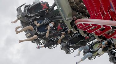 Pengunjung mengenakan masker saat menaiki rollercoaster Vortex di Siam Amazing Park, Bangkok, Thailand, Rabu (17/6/2020). Keseharian warga Bangkok berangsur normal setelah pemerintah terus melonggarkan pembatasan terkait pandemi virus corona COVID-19. (AP Photo/Sakchai Lalit)