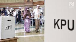Petugas menuntun penyandang disabilitas saat akan melakukan pencoblosan dalam simulasi Pemilu di Jakarta, Kamis (14/2). Simulasi ini diikuti oleh ratusan penyandang disabilitas. (Liputan6.com/Faizal Fanani)