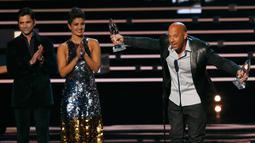 """Vin Diesel menerima penghargaan untuk film favorit dan aksi film favorit bagi """"Furious 7"""" dimana presenter John Stamos dan Priyanka Chopra bertepuk tangan untuk Vin Diesel di People's Choice Awards 2016, Los Angeles (6/1/2016). (REUTERS/Mario Anzuoni)"""
