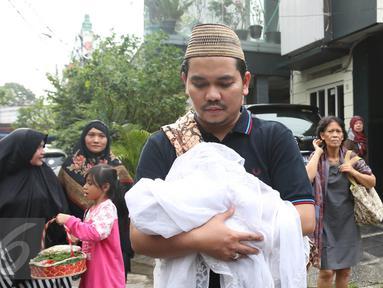 Presenter Indra Bekti menggendong jenazah anak ketiganya menuju TPU Kamboja, Radio Dalam,  Jakarta, Rabu (1/2). Anak ketiga pasangan Indra Bekti dan Aldilla Jelita itu meninggal beberapa menit setelah dilahirkan. (Liputan6.com/Herman Zakharia)