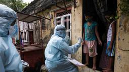 Petugas kesehatan India yang mengenakan alat pelindung diri melakukan pemeriksaan COVID-19 di kawasaan permukiman kumuh di tengah penyebaran wabah tersebut di Mumbai, India (17/6/2020). (Xinhua/Stringer)