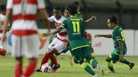 Striker Madura United, Hugo Gomes (kiri) dikurung tiga pemain Persebaya Surabaya dalam laga matchday ke-2 Grup C Piala Menpora 2021 di Stadion Si Jalak Harupat, Bandung, Minggu (28/3/2021). (Bola.com/M Iqbal Ichsan)