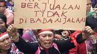 Seorang perempuan memegang poster saat melakukan unjuk rasa bersama ratusan pedagang korban penggusuran di depan halaman kantor Wali Kota Medan.(Antara)