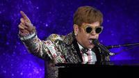 Legenda pop Elton John tampil bernyanyi sambil bermain piano sebelum mengadakan konferensi pers di New York (24/1). Pria 70 tahun ini tercatat sebagai salah satu musisi dengan penjualan terlaris sepanjang masa. (AFP/Timothy A. Clary)