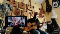 """Pemilik showroom dan bengkel Gitar """"music666"""", Ridwan dan Rudi mendemonstrasikan gitar yang akan dijual secara daring di Ciledug, Tangerang, Rabu (22/7/2020). Pemerintah menargetkan 10 juta usaha mikro kecil menengah (UMKM) pada tahun ini terhubung dengan platform digital (Liputan6.com/Angga Yuniar)"""
