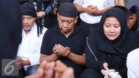 Artis komedi Tukul Arwana bersama anaknya berdoa saat pemakaman istrinya, Susiana, di TPU Tanah Kusir, Jakarta, Rabu (24/8). Susiana wafat di usia 48 tahun akibat penyakit asma yang dideritanya. (Liputan6.com/Immanuel Antonius)