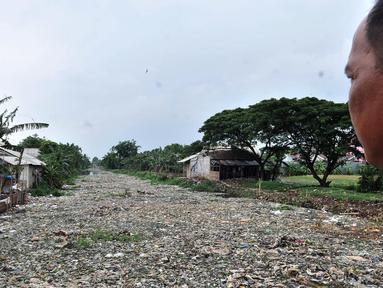 Warga melihat tumpukan sampah yang memenuhi Kali Pisang Batu di Tarumajaya, Kabupaten Bekasi, Jawa Barat, Rabu (9/1). Tumpukan sampah tersebut berasal dari limbah rumah tangga. (Merdeka.com/Iqbal S Nugroho)