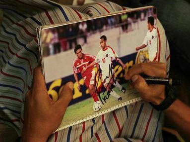 Asisten pelatih Indonesia, Kurniawan Dwi Yulianto, memberikan tanda tangan kepada fans asal Singapura di Hotel Peninsula, Singapura, Jumat (9/11). Indonesia akan melawan Singapura pada laga Piala AFF 2018. (Bola.com/M. Iqbal Ichsan)