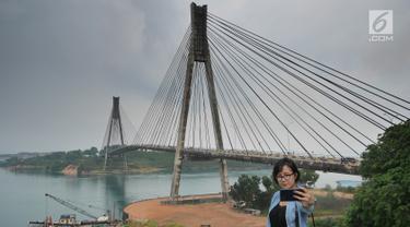 Wisatawan berswafoto dengan latar belakang jembatan Barelang di Batam, Kepri (15/4). Jembatan Barelang adalah singakatan dari Batam, Rempang, dan Galang. (Liputan6.com/Herman Zakharia)
