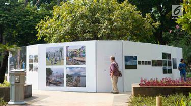 Pengunjung mengamati foto yang dipajang dalam pameran bertajuk 'Identitas' pada acara Jakarta International Photo Festival (JIPFest) 2019 di Taman Menteng, Jakarta, Rabu (3/7/2019). JIPFest 2019 menghadirkan 50 fotografer internasional. (Liputan6.com/Immanuel Antonius)