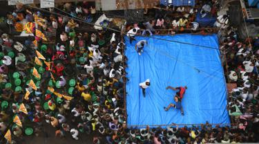 Pegulat amatir India bertarung saat mengikuti kompetisi untuk menyambut perayaan Diwali di Kolkata, India (18/10). Pertandingan gulat ini digelar di tengah jalan yang padat di daerah Kolkata. (AFP Photo/Dibyangshu Sarkar)