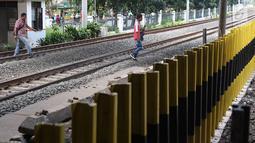 Pejalan kaki menyeberangi perlintasan kereta api di Tanjung Barat, Jakarta, Senin (7/1). Meskipun sering terjadi kecelakaan dan dipasangi pagar, pejalan kaki tetap melompati pagar dari pada menggunakan fasilitas JPO. (Liputan6.com/Immanuel Antonius )