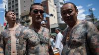 Peserta dengan tato tradisional di tubuhnya mengikuti Festival Sanja Matsuri di luar kuil Sensoji, distrik Asakusa, Tokyo, Minggu (20/5). Dan hanya di Festival ini para Yakuza menampakkan diri dan berbaur dengan masyarakat lainnya. (AFP/Behrouz MEHRI)