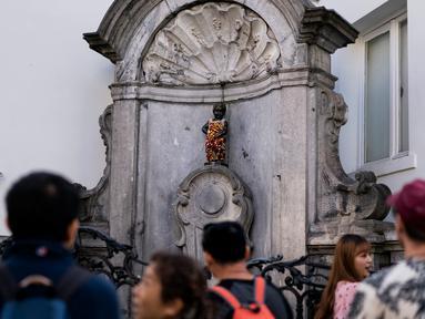 Wisatawan berfoto dekat patung 'Manneken Pis' dalam balutan baju bermotif bunga di ibu kota Belgia, Brussels, Senin (12/8/2019). Patung anak laki-laki yang sedang buang air kecil ini menjadi salah satu daya tarik uta di kota cantik tersebut. (Photo by Kenzo TRIBOUILLARD / AFP)