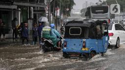 Sejumlah kendaraan melintasi genangan air di Jalan Medan Merdeka Timur, Jakarta, Jumat (24/1/2020). Hujan deras yang mengguyur Jakarta sejak pagi tadi mengakibatkan genangan air di Jalan Medan Merdeka Timur. (Liputan6.com/Faizal Fanani)